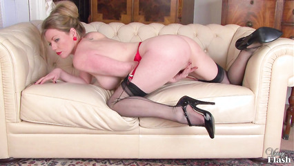 Женщина эротично снимает с себя одежду и ласкает промежность